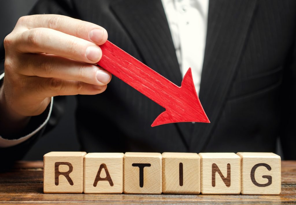 A man holds a red down arrow above the word Rating